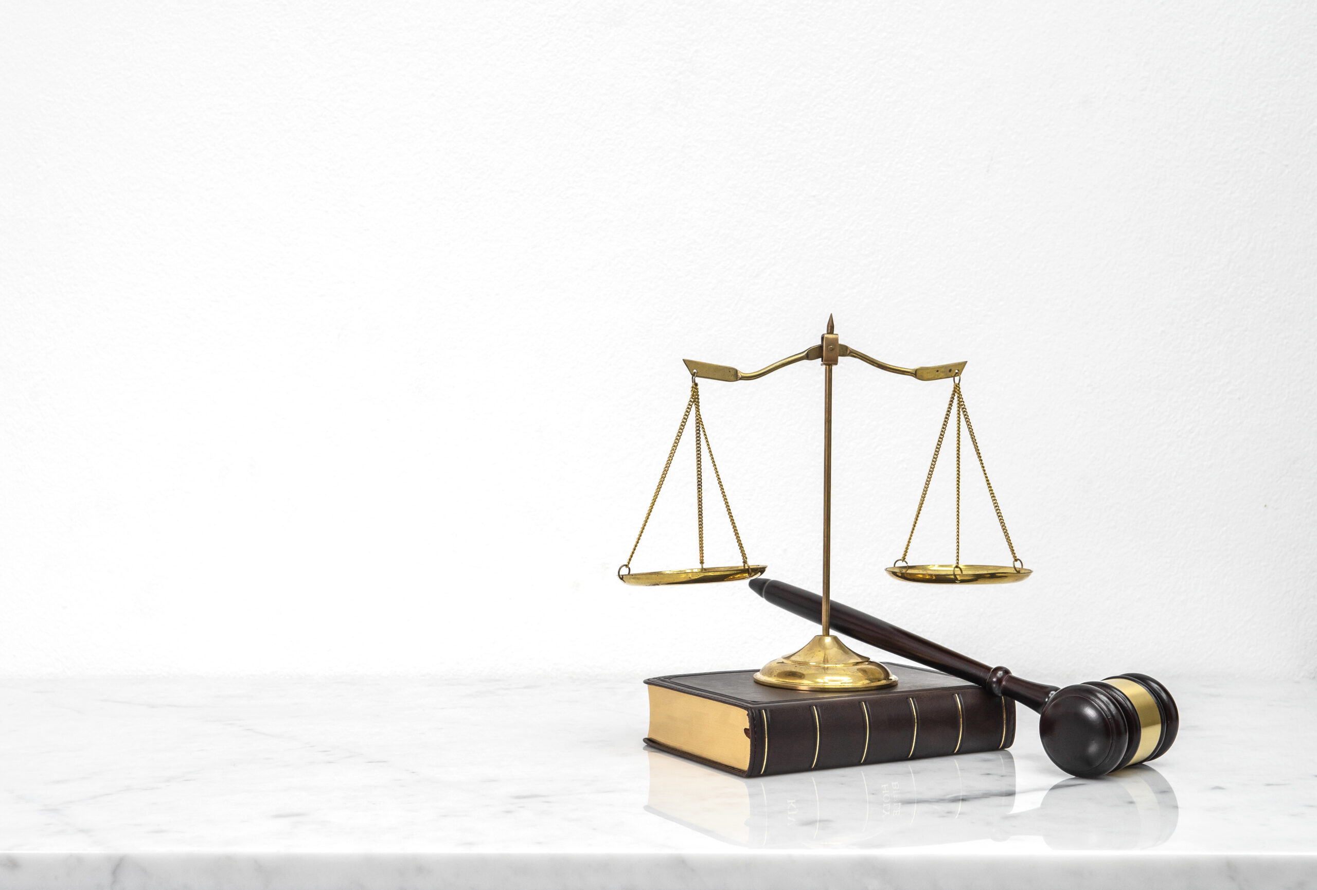 Wooden gavel and law book put on white marble table top counter